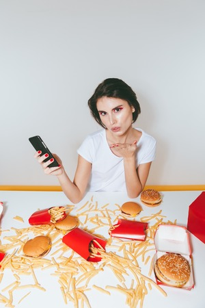 disinclination: Cute young woman using cell phone and sending kiss at the table with fast food over white background Stock Photo