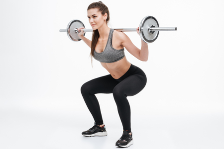 Portrait of a focused smiling fitness woman doing squats with barbell isolated on a white background Stock Photo