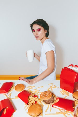 Lovely young woman with white mug sitting and refusing from fast food over white background