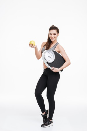 Full length portrait of a happy smiling fitness woman standing, holding an apple and scales isolated on a white background Stock Photo
