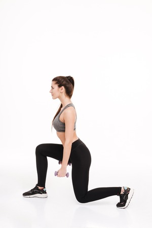 Side view portrait of a young pretty sportswoman doing squats with dumbbells isolated on a white background