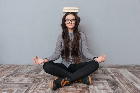 well head: Young cute Asian woman meditating on the floor with books on the head as well as with eyes closed. Isolated gray background