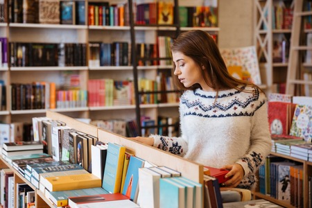 Portrait of a young casual woman searching for a book in bookstore and looking at camera 스톡 콘텐츠