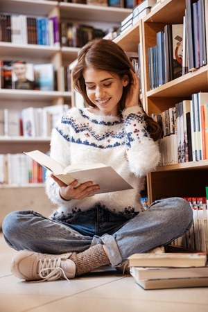Young female student sitting on library floor reading book in college