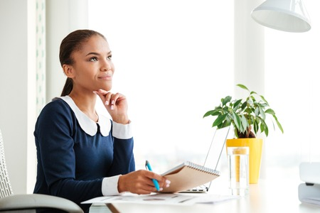 Smiling pensive african business woman in dress sitting on workplace in office. Side view Фото со стока