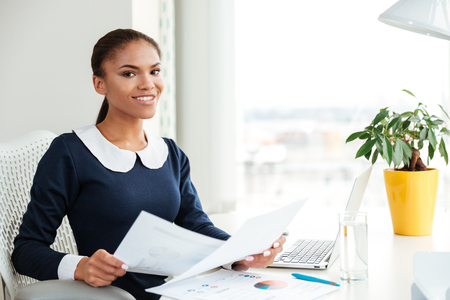 Smiling african business woman in dress sitting on workplace with documents near the window and looking at camera in office