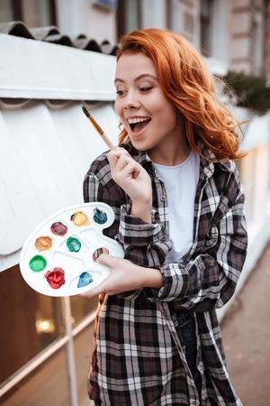 easel: Picture of happy young lady painter with red hair walking on the street. Look at palette while holding paintbrush outdoors.