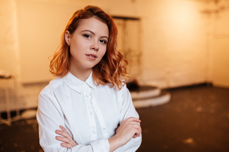 Image of serious redhead young woman dressed in white shirt looking at camera with arms crossed. Stock Photo