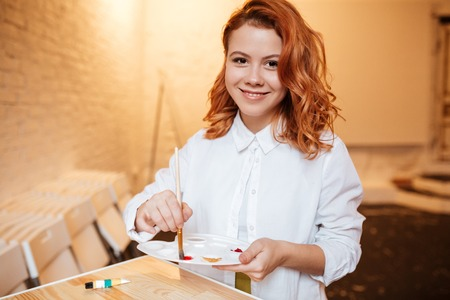 young adult woman: Picture of happy young redhead woman painter with oil paints and palette. Look at camera.