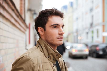 通りを歩いてよそ見集中の若い男の写真。 写真素材