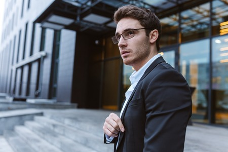 Business man in suit and glasses standing sideways near the office