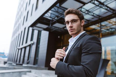 ビジネス スーツと眼鏡の横に立って、オフィスの近くのカメラ目線で男の画像下から