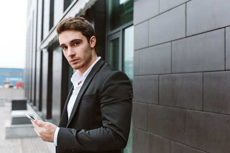 near side: Side view of business man in suit standing outdoors with phone near the office and looking at camera Stock Photo