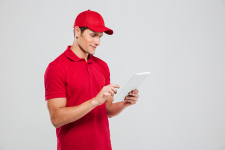 Side view of delivery man with tablet. isolated gray background