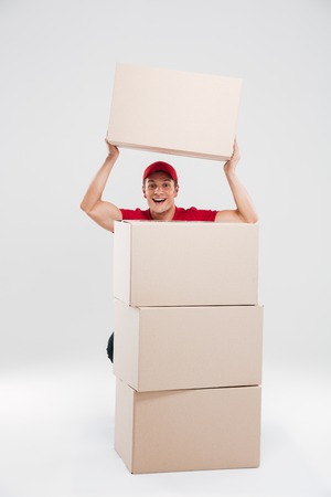 Young delivery man behind the boxes. so funny. isolated gry background