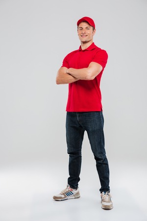 Deliveryman with arms crossed in studio. looking at camera. Full length portrait. isolated gray background Stok Fotoğraf