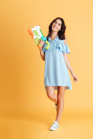 Full length portrait of a beautiful smiling woman in blue dress holding water gun isolated on a orange background Stock Photo