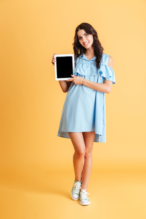Full length portrait of a smiling casual woman showing blank tablet computer screen isolated on a orange background Stock Photo