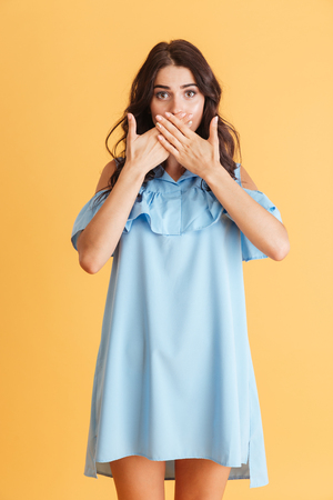 Full length portrait of a surprised woman covering her mouth with hands over orange background