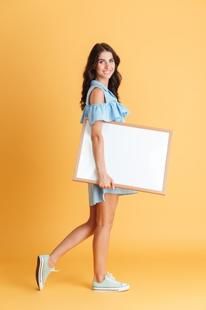 Side view of a cheerful smiling woman holding white blank board isolated on the orange background Stock Photo