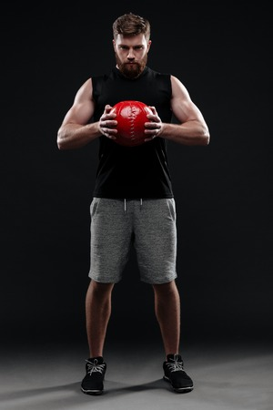 Full length image of trainer with ball. holding ball in hands