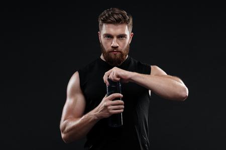 Athletic homme avec une bouteille. tellement sérieux. regardant la caméra