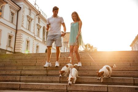 down the stairs: joven pareja caminando por las escaleras con sus perros en una calle de la ciudad