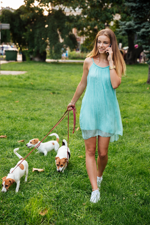 retractable: Attractive young woman talking on the mobile phone while walking her dogs in the park Stock Photo