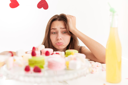 Sad upset young woman looking at sweests on the table