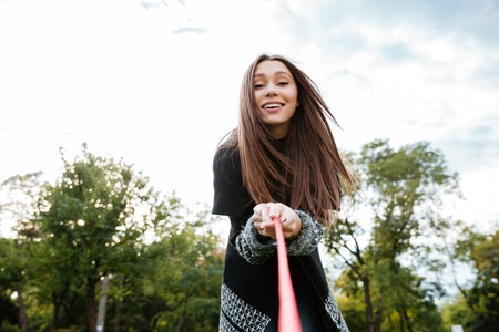 endear: Cheerful pretty young woman with dog on leash in park Stock Photo