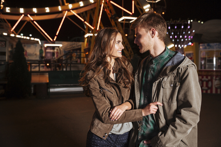 Young cheerful couple in amusement park. in warm clothes
