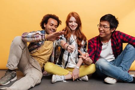 Gruppo di giovani sorridenti seduta e giocare Rock Paper Scissors su sfondo giallo Archivio Fotografico - 70110855