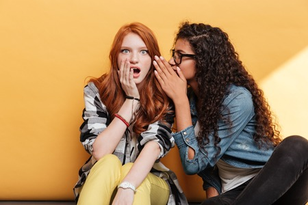 Two lovely young women talking and telling secrets over yellow background Stok Fotoğraf