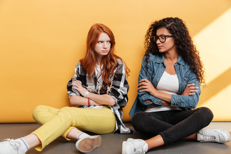 squabble: Two sad offended young women sitting with arms crossed over yellow background