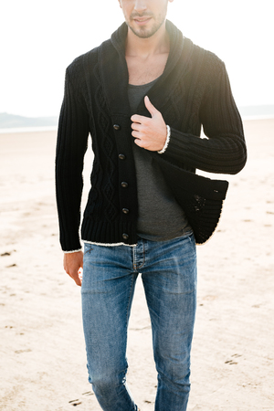 Cropped image of a young casual man walking at the beach in the sunlight