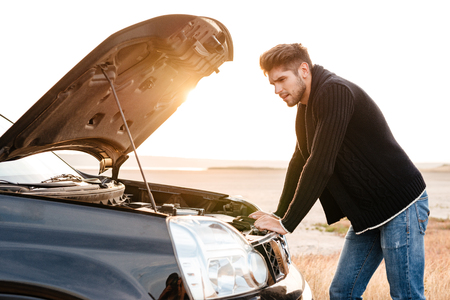 Young upset casual man trying to fix his broken car outdoors Stock Photo
