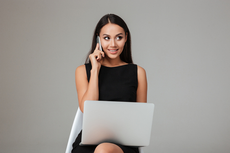 modern businesswoman: Happy young businesswoman sitting on the chair with laptop and talking on mobile phone over gray background