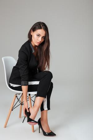 カメラ目線の椅子にはかなりファッションモデル。灰色の背景 写真素材