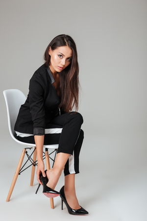 Pretty fashion model on chair looking at camera. gray background Stock Photo