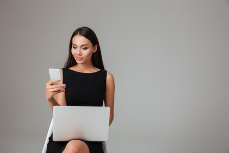 modern businesswoman: Smiling young businesswoman sitting on the chair with laptop and talking on mobile phone over gray background