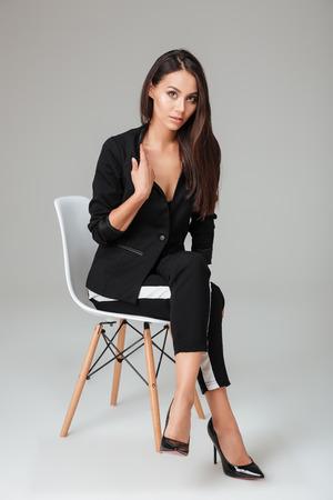 Modelo bonito en la silla que mira la cámara. Moda. fondo gris