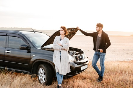 Upset young couple standing near car with open hood outdoors Stock Photo