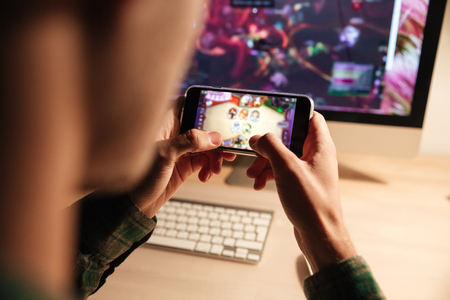 Closeup of man playing videogame on smartphone in the evening at home