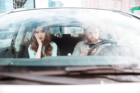 Young couple in car. girl is not happy