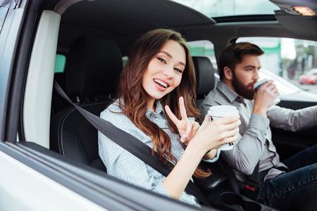 Glimlachend paar in auto met koffie. meisje camera kijken. man aan het stuur. zijaanzicht Stockfoto