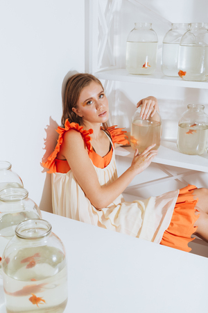 gold fish bowl: Pretty young woman sitting and holding gold fish in jar in the room