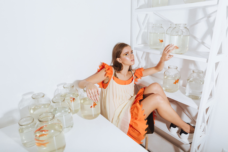 Attractive young woman sitting and relaxing near closet and table with gold fishes in jars Stock Photo