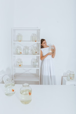 gold fish bowl: Cute young woman standing in the room and holding gold fish in jar
