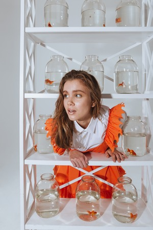 aquarist: Lovely amusing young woman standing and leaning on the shelf with gold fishes in jars