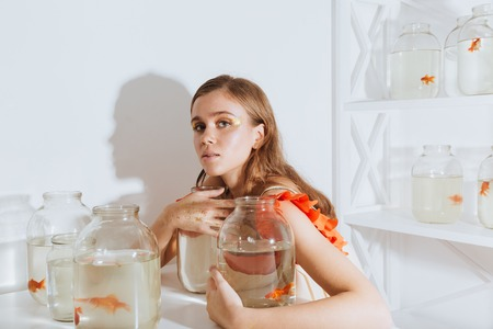 Lovely young woman sitting and holding gold fishes in jars at the table